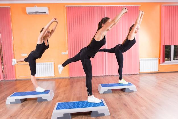 Drei fitte mädchen, die gleichgewichtsübungen mit einem bein auf aeroben step-plattformen im fitnessstudio machen.