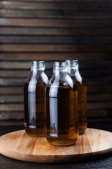 Drei flaschen frischer hölzerner hintergrund des getränks