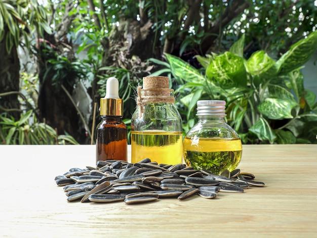 Drei flaschen kaltgepresstes sonnenblumenöl mit samen