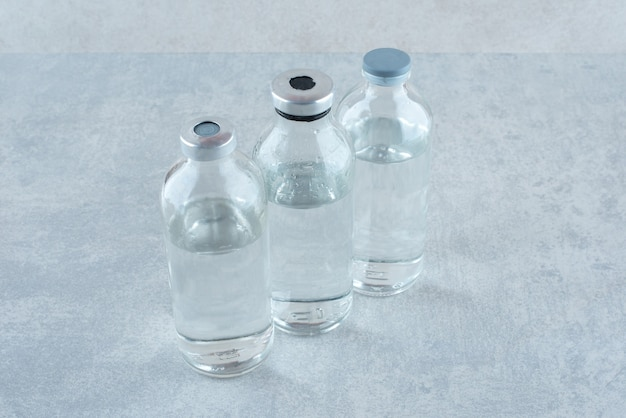 Drei flaschen medizinisches ethanol auf grauer oberfläche