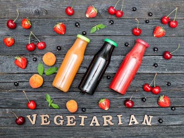 Drei flaschen mit saft, frucht und aufschrift vegetarier auf schwarzem hölzernem hintergrund. food-konzept