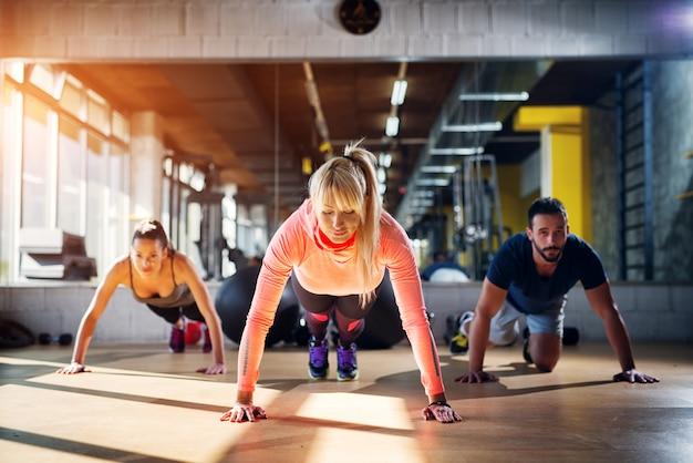 Drei fokussierte sportler bereiten sich auf liegestütze im fitnessstudio vor.