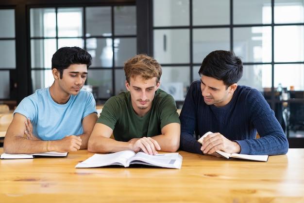 Drei fokussierte studenten, die zusammen lehrbücher am schreibtisch lesen