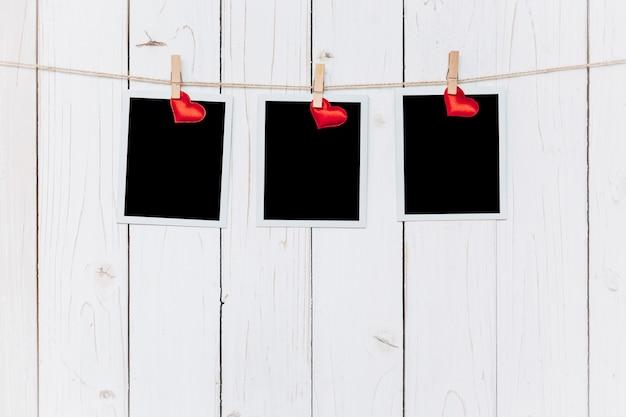 Drei fotorahmen leer und rotes herz hängen auf weißem holz hintergrund mit platz