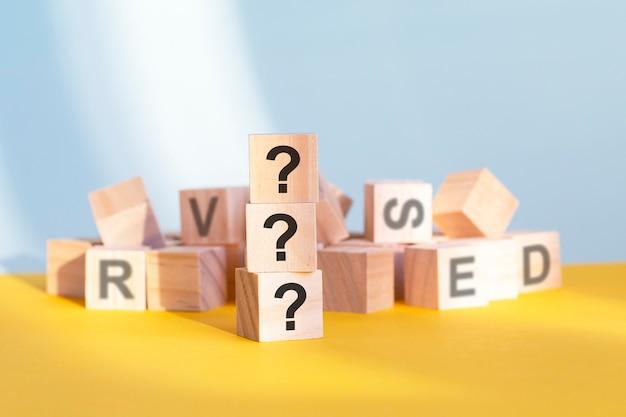 Drei fragezeichen auf holzwürfeln - angeordnet in einer vertikalen pyramide, grauem und gelbem hintergrund, geschäfts- und bildungskonzept