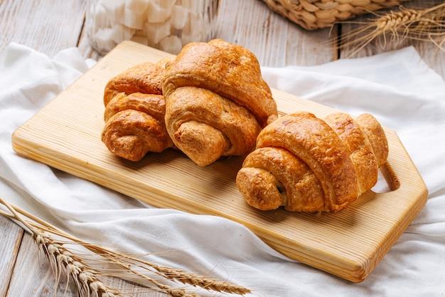 Drei französische croissants auf dem hölzernen schneidebrett, verziert mit weizen und serviette