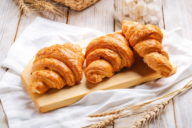 Drei französische croissants auf dem holzbrett