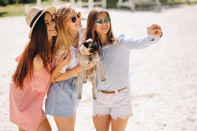 Drei frauen am strand mit kleinem hund