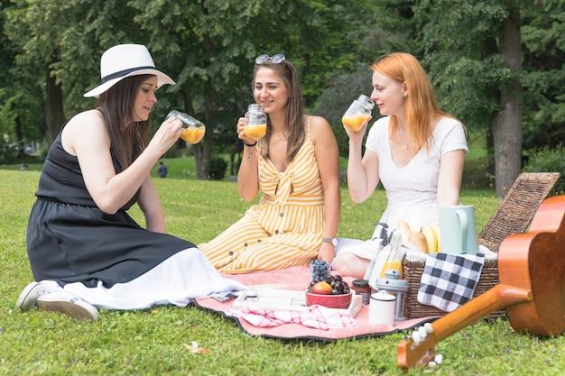 Drei frauen, die den gesunden saft im park genießen