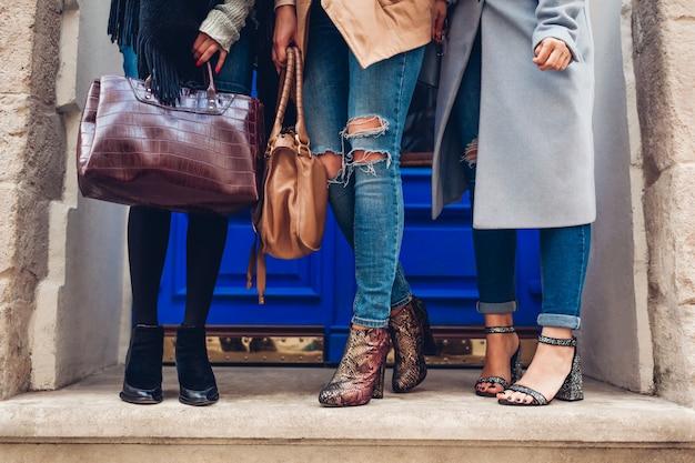 Drei frauen, die draußen stilvolle schuhe und accessoires tragen. herbstmodekonzept. damen, die moderne weibliche handtaschen halten