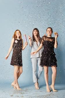 Drei frauen feiern den feiertag mit spaß beim lachen und kuchenessen unter dem fliegenden konfetti. mädchen posieren und lächeln auf blauem hintergrund, fröhliche emotionen, kein fokus no