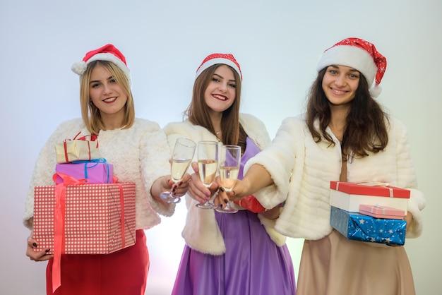 Drei frauen in eleganten kleidern und weihnachtsmützen mit champagnergläsern. frohe weihnachten-konzept.