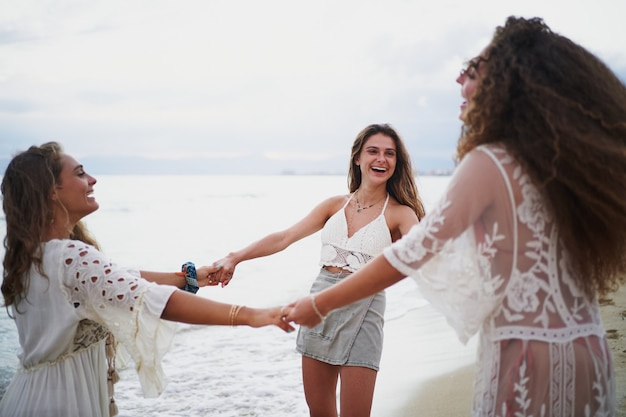 Drei frauen machen einen kreis und drehen sich zusammen, während sie lachen und spaß am strand haben