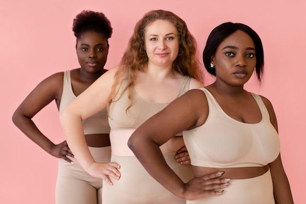Drei frauen posieren, während sie einen körperformer tragen