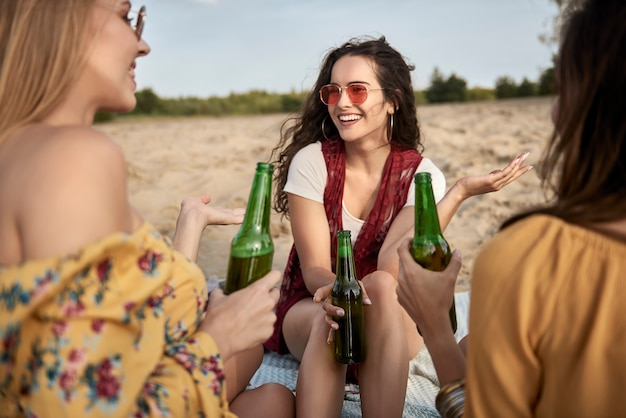 Drei frauen sitzen am strand und trinken bier