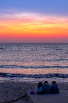 Drei frauen warten auf den sonnenaufgang vor dem meer (region apulien, süditalien). konzept der freundschaft, reisen und abenteuer.