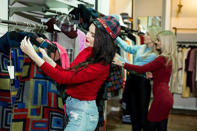 Drei freudige junge frauen, die warme jacken im bekleidungsgeschäft einkaufen.