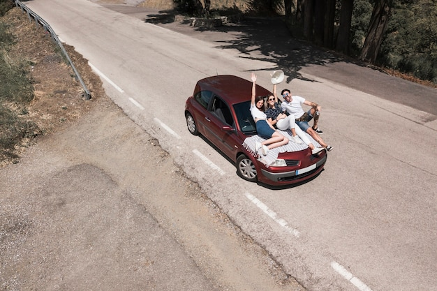 Drei freunde, die auf der autohaube genießt die reise sitzen