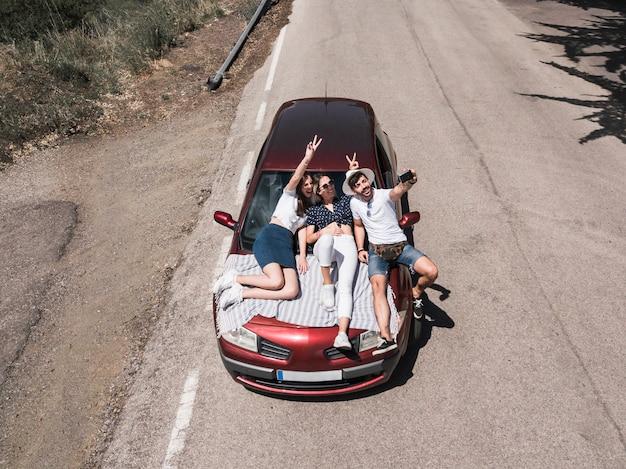 Drei freunde, die auf der autohaube nimmt selbstporträt sitzen