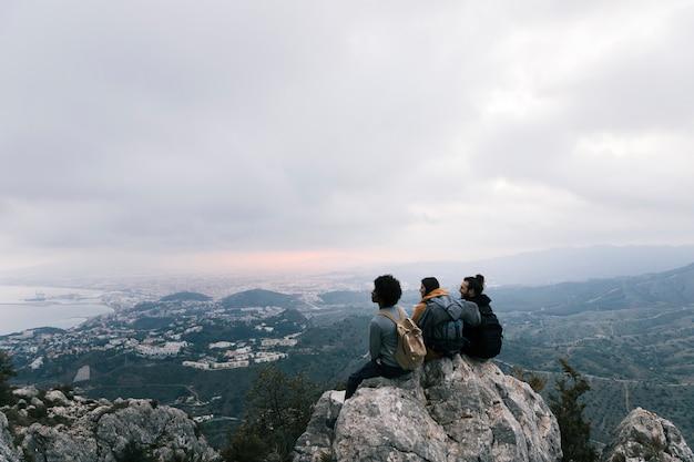 Drei freunde, die auf die oberseite des berges sitzen, die szenische ansicht genießend