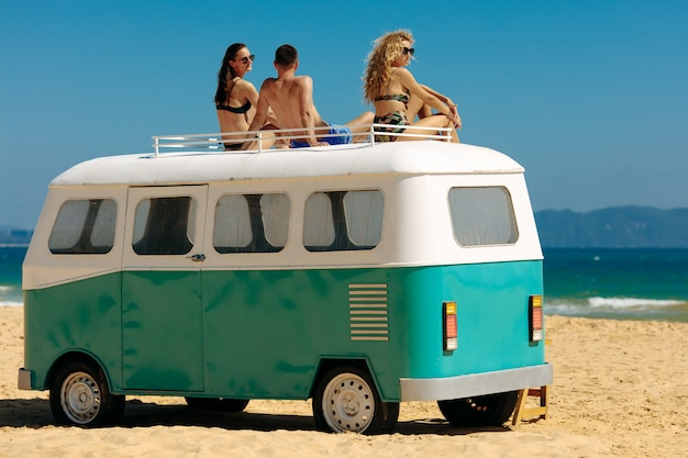 Drei freunde, die oben auf retro-bus an der küste entspannen