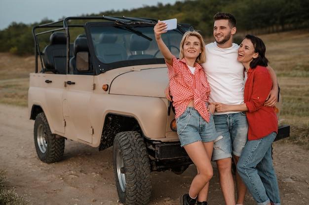 Drei freunde, die selfie nehmen, während sie mit dem auto reisen