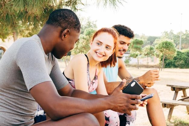 Drei freunde entspannen sich und unterhalten sich nach dem training im freien