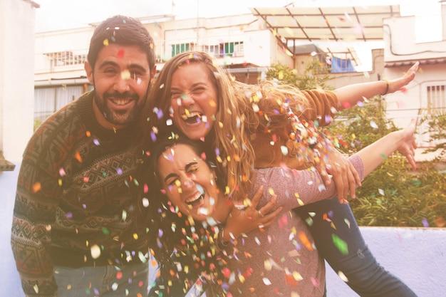 Drei freunde genießen auf der dachterrasse und werfen konfetti.