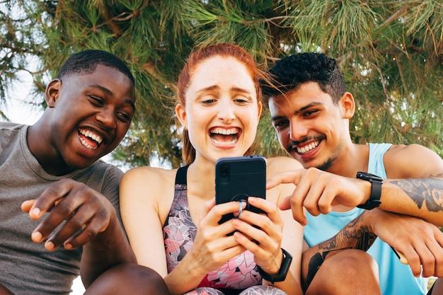 Drei freunde schauen nach dem training im freien auf das smartphone