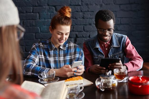 Drei freunde verbringen eine schöne zeit miteinander, unterhalten sich im café, essen dessert und trinken tee. menschen, lebensstil
