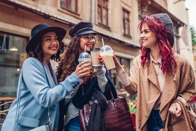 Drei freundinnen, die draußen getränke haben. frauen, die mit kaffee, orangensaft und teetassen klirren