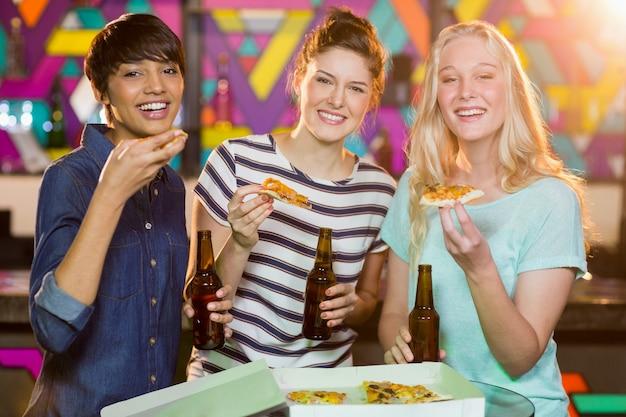 Drei freundinnen, die eine flasche bier und eine pizza in der partei haben