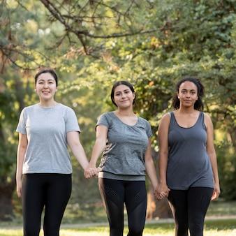 Drei freundinnen, die hände am park halten
