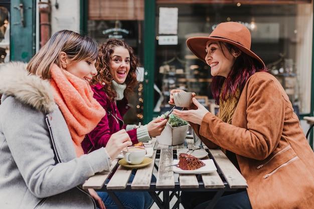 Drei freundinnen, die kaffee in einer terrasse in oporto, portugal trinken. ein lustiges gespräch führen
