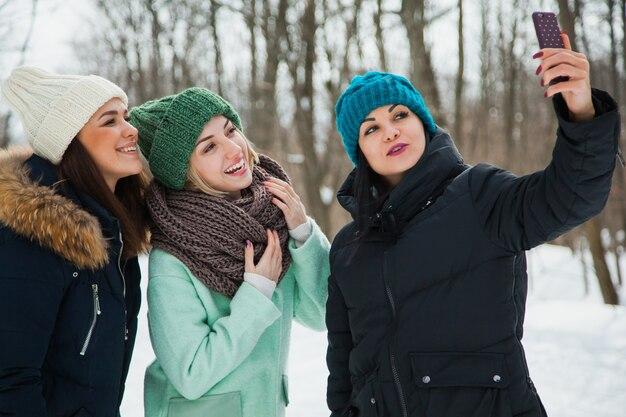 Drei freundinnen draußen in strickmützen an einem schneekalten winterwetter. lächelnde mädchen in warmen kleidern machen selfie auf schnee