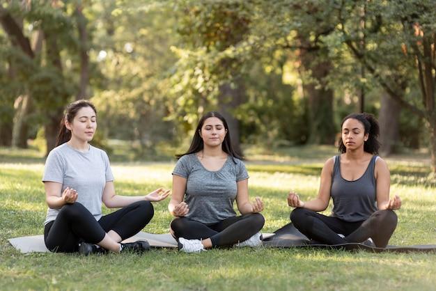 Drei freundinnen machen yoga im park