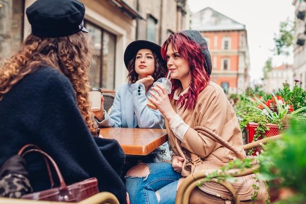 Drei freundinnen mit getränken im café im freien. frauen plaudern und hängen während der kaffeepause zusammen