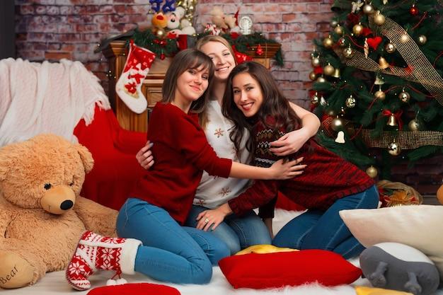 Drei freundinnen umarmen sich vor dem hintergrund der weihnachtsdekoration