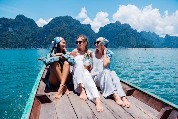 Drei freundinnen von touristen reisen um khao sok nationalpark, im urlaub in thailand. segeln auf asiatischem boot auf see am sonnigen tag, mit herrlicher aussicht.