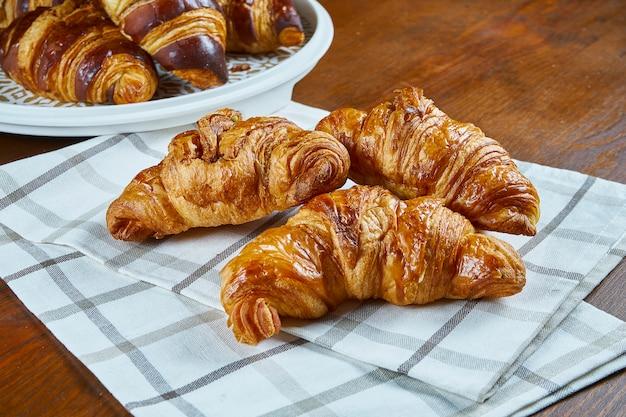 Drei frisch gebackene croissants auf beigem stoff auf einem holztisch. lebensmittelfotografie für bäckerei-cafés. nahaufnahme.