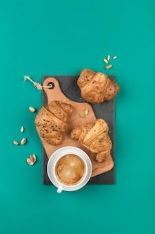 Drei frisch gebackene croissants auf einem holzbrett mit einer tasse kaffee auf grün