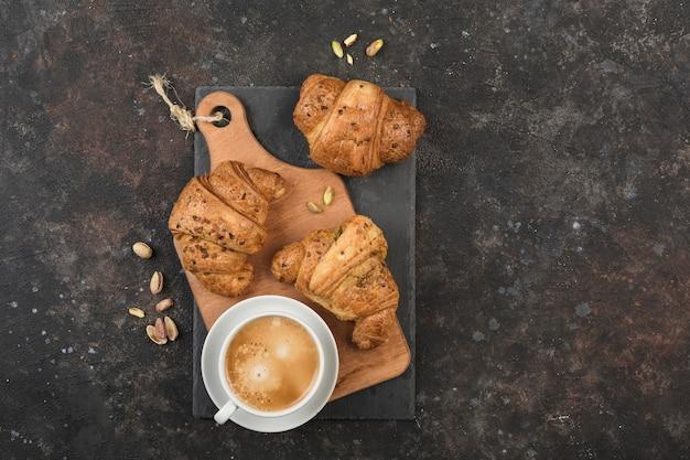 Drei frisch gebackene croissants auf einem holzbrett mit einer tasse kaffee