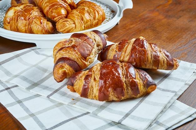 Drei frisch gebackene croissants mit schokolade auf beigem stoff auf einem holztisch. lebensmittelfotografie für bäckerei-cafés. nahaufnahme.