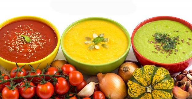 Drei frische bunte gemüsesuppenpüree - tomate, kürbis und grüne erbsen auf einem weißen hintergrund schließen