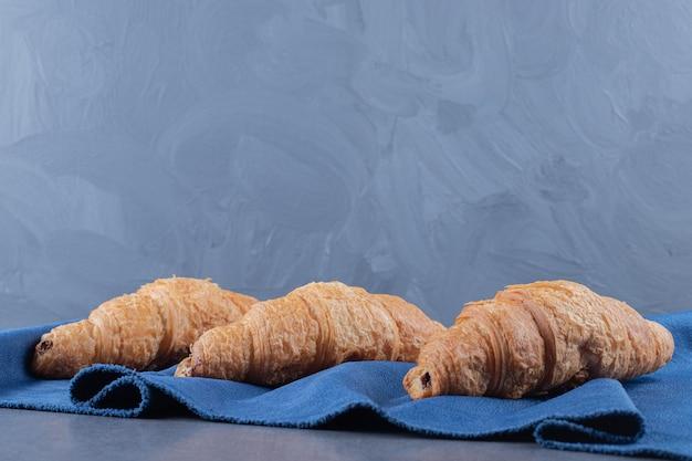 Drei frische französische croissants auf blauer serviette.