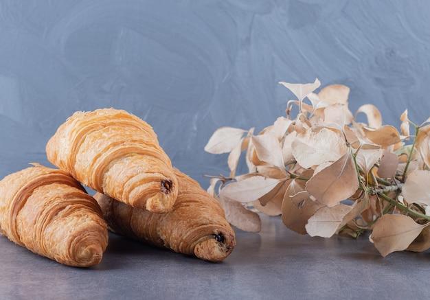 Drei frische französische croissants auf grauem hintergrund.