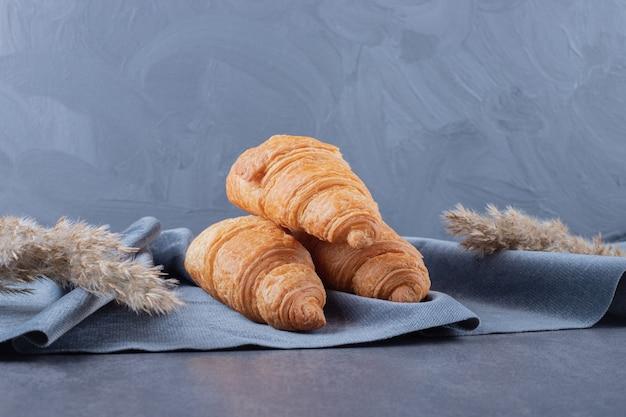 Drei frische französische croissants auf grauer baumwollserviette.