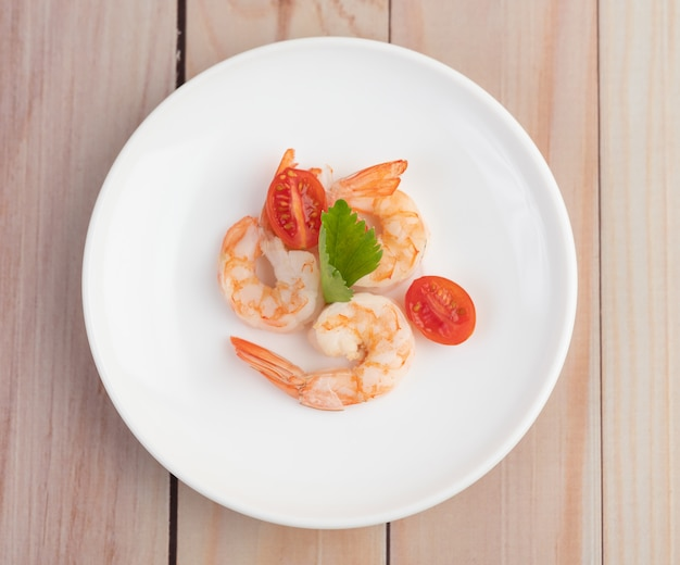Drei frische garnelen und halbe tomaten in einem weißen teller auf einem holz.