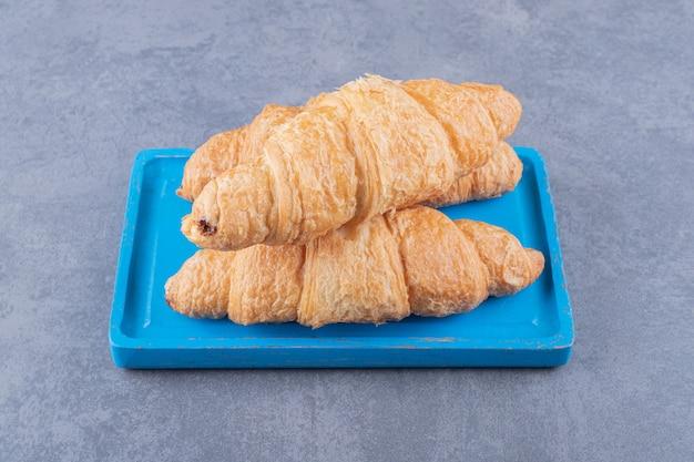 Drei frische hausgemachte croissants auf blauem holzbrett.