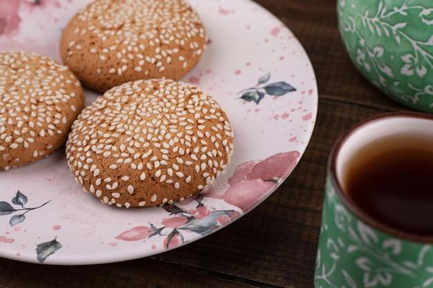 Drei frische kekse mit tasse tee auf holztisch.